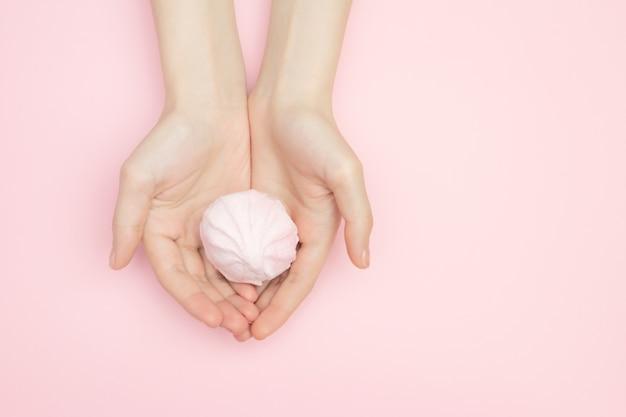 Женщина любовника конфет вручает держать зефир на розовой поверхности с космосом экземпляра.