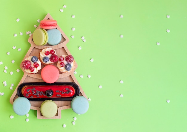 Sweets macaroons and cakes in plate in a shape of christmas tree