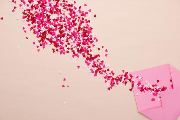 緑の背景の上の封筒に甘い砂糖菓子の心