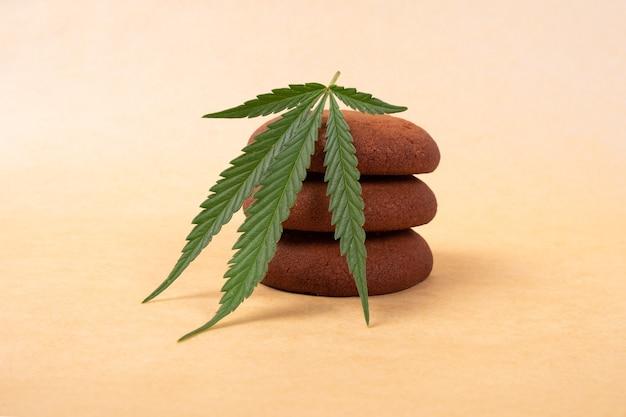 マリファナのお菓子、黄色の背景に大麻植物の葉とチョコレートチップクッキー。