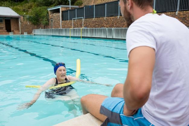 수영장가에서 고위 여자와 상호 작용하는 수영 코치