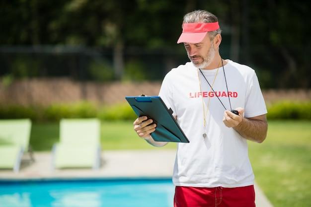 プールサイド近くのクリップボードを見てコーチを泳ぐ