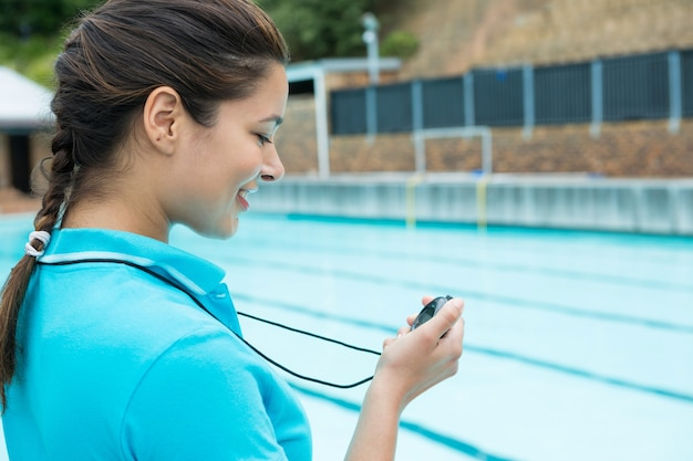 레저 센터에서 수영장 근처의 스톱워치를보고있는 수영 코치