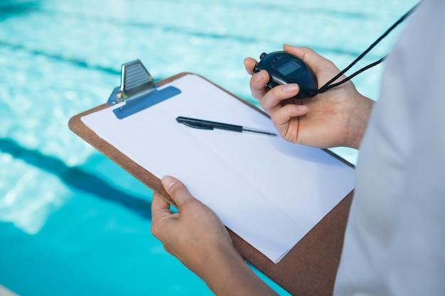 Тренер по плаванию смотрит на секундомер у бассейна