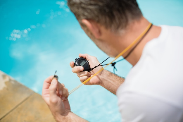 Swim coach looking at stop watch near poolside