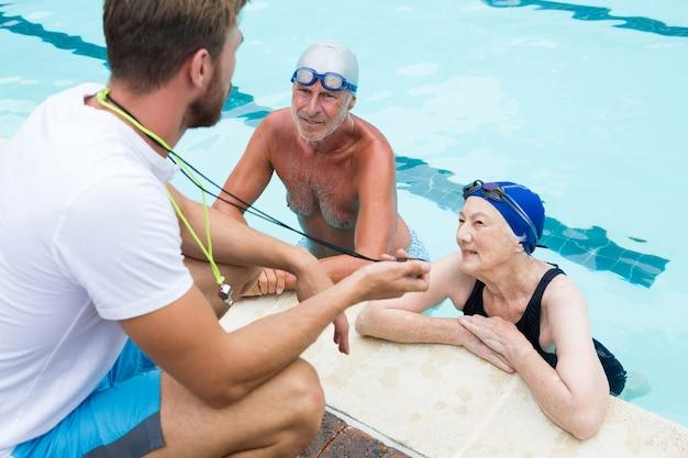 Swim coach showing stop watch to senior couple at poolside
