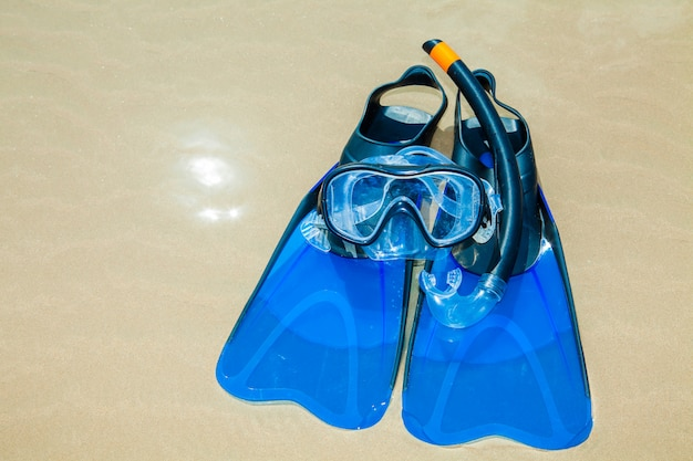 Swim flippers, mask, snorkel, hat in the surf on the sandy beach