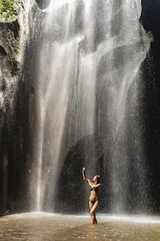 즐겁게 수영하십시오. 동굴 근처 물에 있는 동안 그녀의 모습을 보여주는 기뻐하는 피트니스 여성