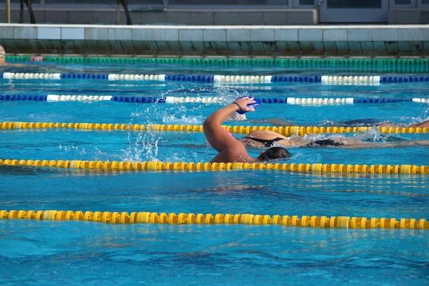 大きな屋外スイミングプールで泳ぐ