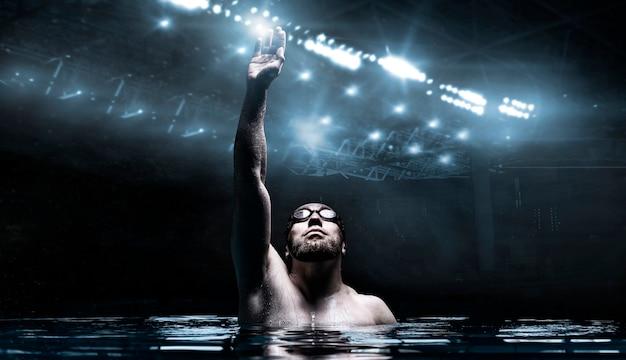 Пловец в бассейне поднимает руки вверх.