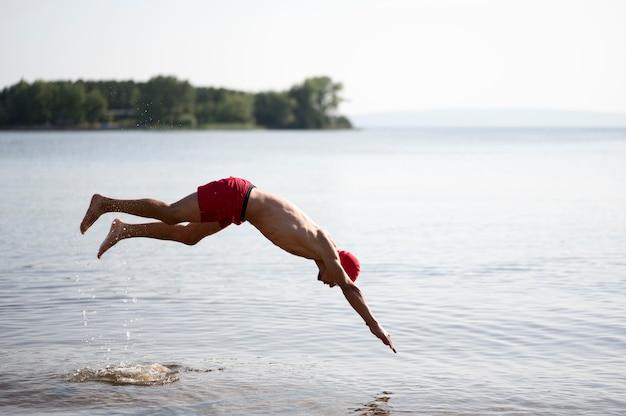 Пловец прыгает в озере
