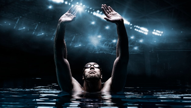 Swimmer in the pool raises his hands up.  arena with flashes.