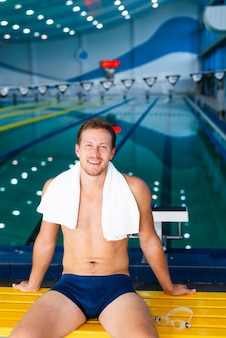 Swimmer posing with towel on his shoulders