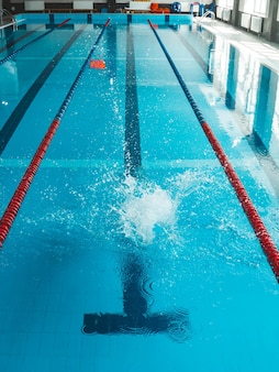 The swimmer pushes off the edge of the swimming pool