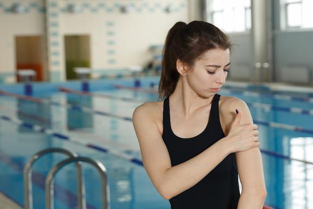 プールサイドの近くに立って泳ぐ瞬間の前に肩の痛みを持つスイマースポーツマン。スポーツ傷害の概念