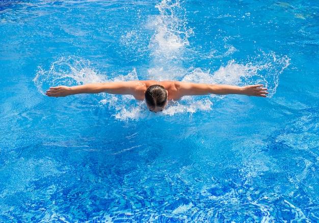 Пловец плавает в бассейне со стилем бабочки
