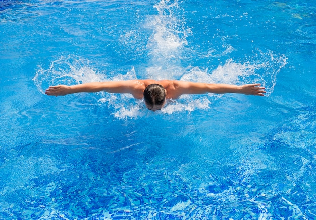 Swimmer swiming in pool with butterfly style
