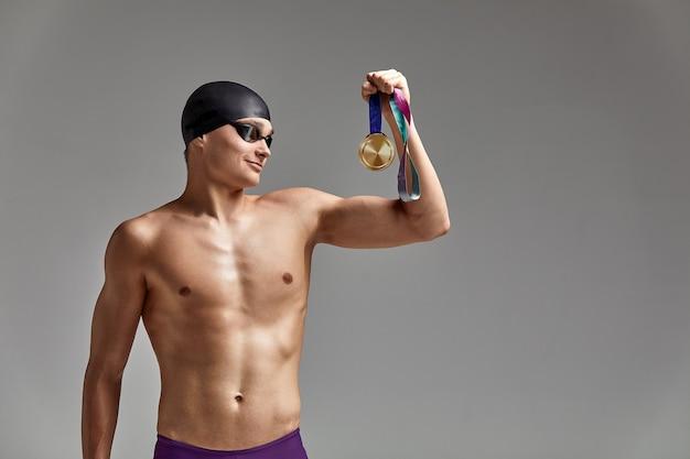 灰色の背景にメダルを持ったスイマーは勝利を喜ぶ。優れた体型のアスリートは、メダルを手に持って勝利を祝う。勝利のコンセプト、灰色の背景、コピースペース。