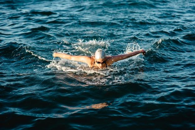 Пловец с кепкой и очками плавает в воде