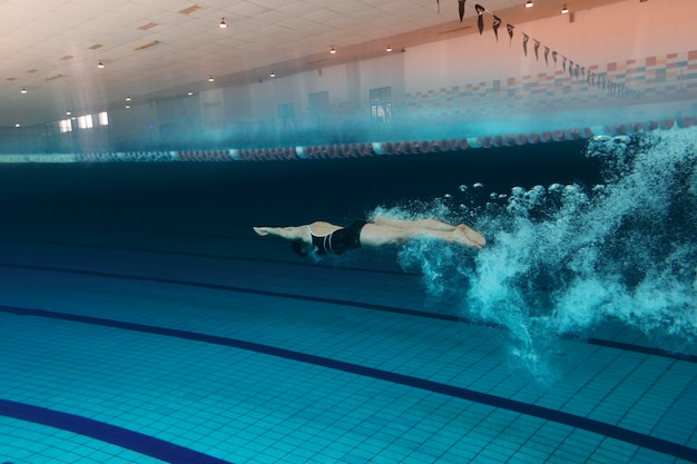 Пловец с оборудованием в бассейне, полный кадр