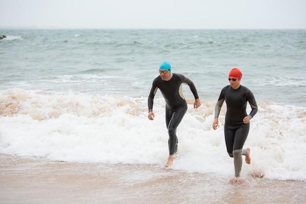 Пловцы в гидрокостюмах бегут по морским волнам