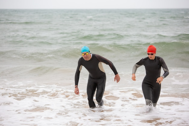 Swimmers in wetsuits in sea waves
