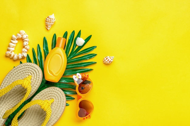 Swimming accessories - sunblock, heart - shaped glasses, flip flop, palm, shells isolated. flat lay