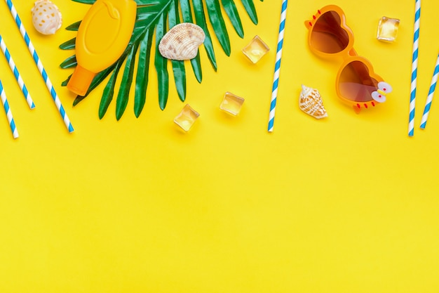 Swimming accessories - sunblock, heart - shaped glasses, ice cube, palm, shells, drinking paper straws for party with blue stripes isolated. flat lay top view