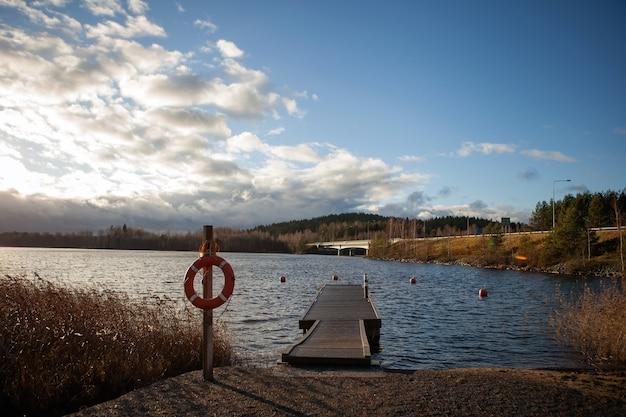 다리가 있는 호수 근처의 수영 지역. 푸른 차가운 물과 흐린 하늘. 핀란드의 자연.