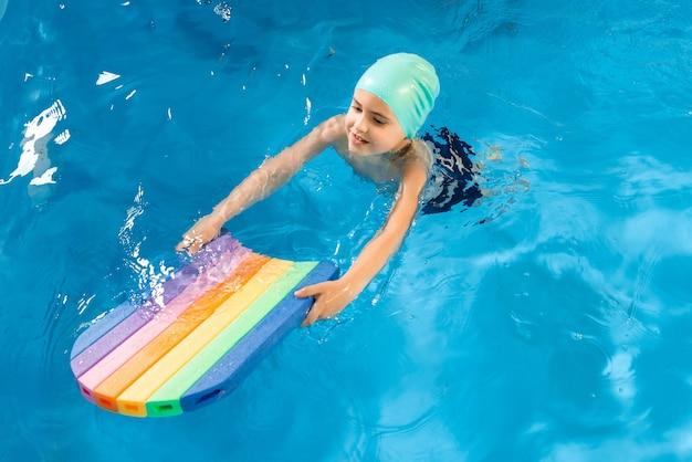 Урок плавания. крупным планом детей, практикующих флаттер-удар с доской в бассейне