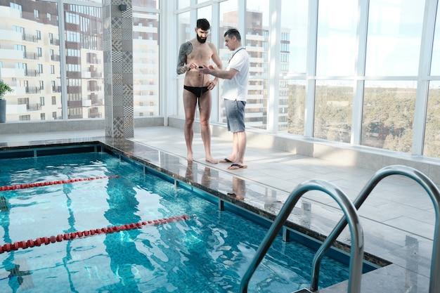 수영 코치에게 스피드 개발 방법을 설명하면서 스톱워치에서 랩 타임을 보여주는 수영 코치