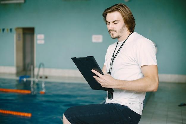수영장 옆에 서 있는 수영 코치. 수영 기록을 확인합니다. 클립보드를 들고.