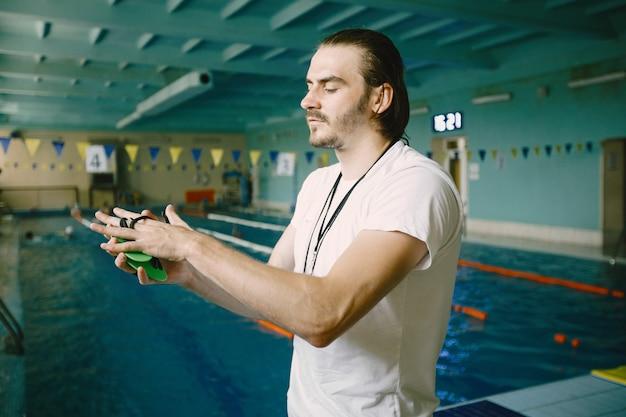 スポーツマンのための水泳用具。プールサイドに立つ男性コーチが、水泳用ハンドパドルの使い方をご案内します。