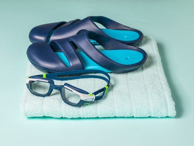 Swimming glasses on a blue towel. accessories for swimming in the pool.