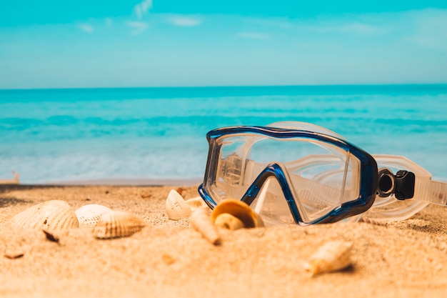 Swimming goggles on sandy beach