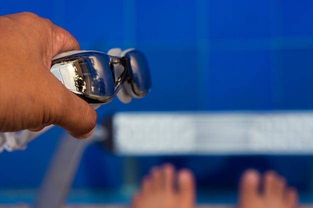 Плавательные очки, удерживаемые пловцом на плавательном бассейне