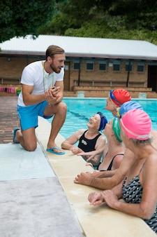 수영장가에서 수석 수영을 돕는 수영 강사