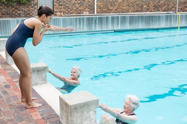 수영장에서 노인 여성을 돕는 수영 강사