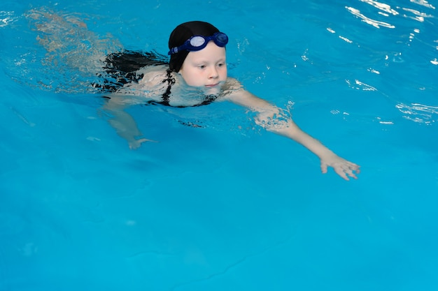 Swimming lessons for children in the pool - beautiful fair-skinned girl swims in the water