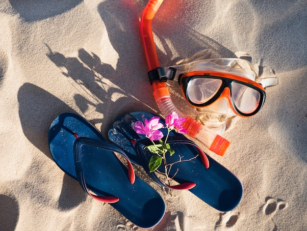 Swimming mask and flip-flops on sand. top view