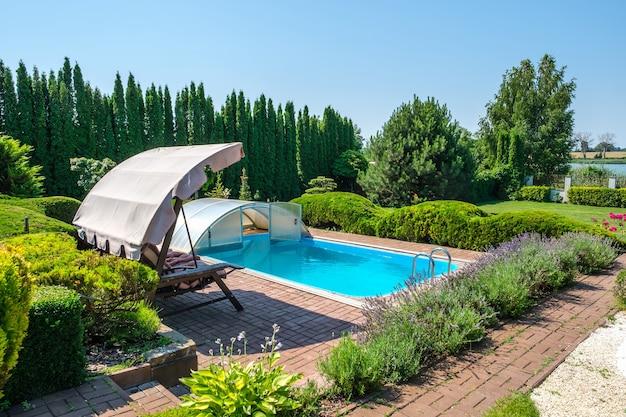 Бассейн и сад с красиво подстриженными кустами и садовыми качелями на заднем дворе. ландшафтный дизайн. фото высокого качества