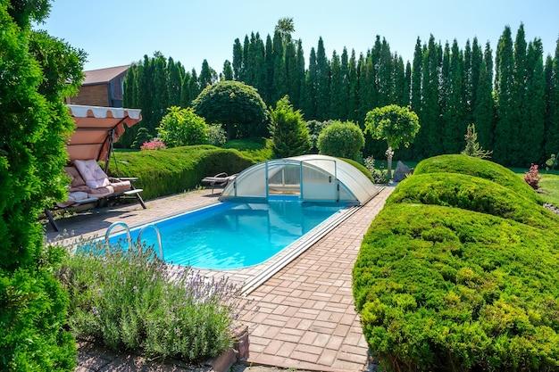 Бассейн и сад с красиво подстриженными кустами и камнями на заднем дворе. ландшафтный дизайн. фото высокого качества