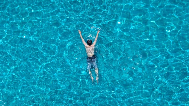 スイミングプールの青い色の澄んだ水と夏の晴れた日とトップビューの角度で楽しんでいる人々。