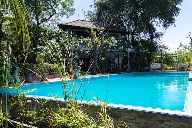 Бассейн с голубой водой и тропический сад с видом на море