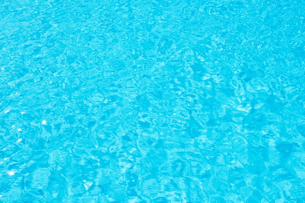Swimming pool blue water surface with bright sun light reflection.