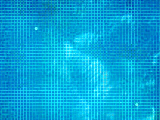 맑은 물 표면에 나무 그림자가있는 작은 사각형 파란색 모자이크 타일이있는 수영장 바닥