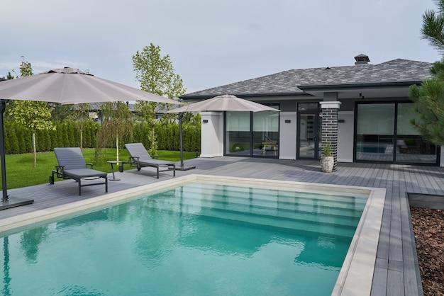 Дизайн бассейна в современной резиденции. современная терраса с зонтиками, шезлонгами и бассейном. на территории никого нет