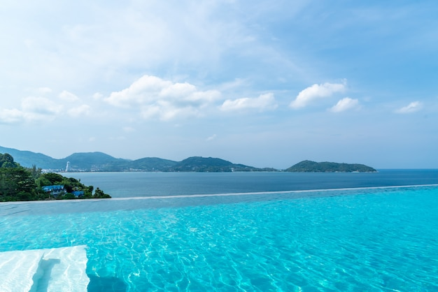 Swimming pool in hotel and resort with sky and sea
