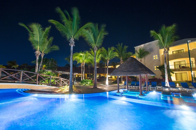 Бассейн в ночном освещении. тропический курорт ночью