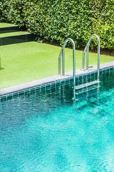 草の背景とプールのはしご
